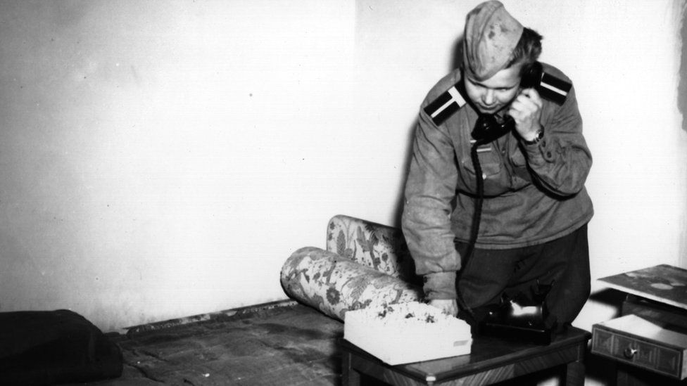 """A Russian soldier using Eva Braun""""s phone in her bedroom in Hitler""""s shelter, at the Chancellery building, Berlin"""