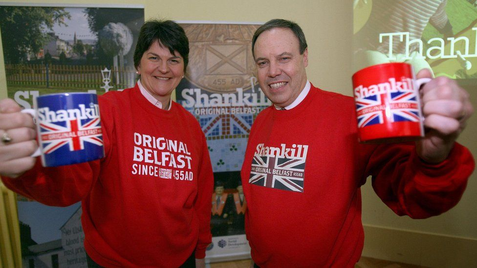 Arlene Foster and Nigel Dodds wearing Shankill-branded sweaters and holding Shankill-branded mugs in 2008