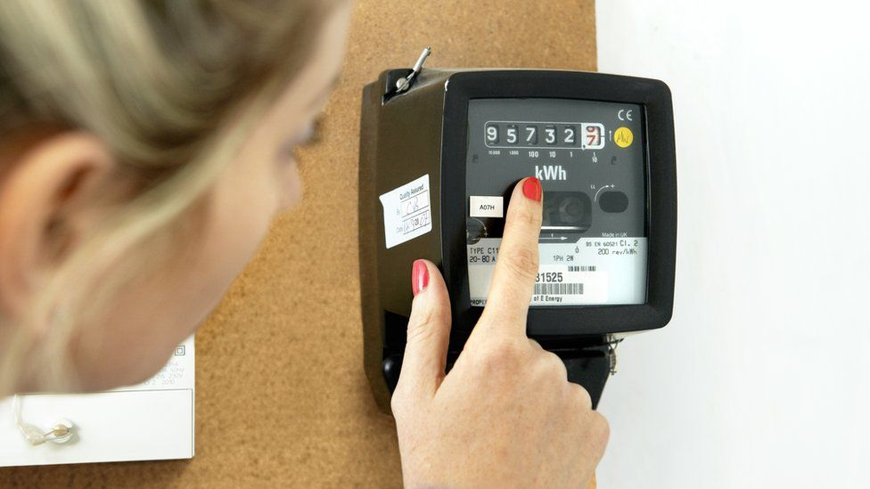 Woman examines energy meter