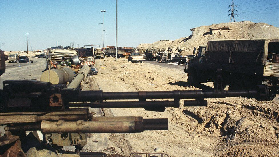 Abandoned cars and trucks clog the road leading out of Kuwait City after the retreat of Iraqi forces from the city. In the foreground is an Iraqi anti-aircraft gun, damaged in one of the final attacks by Coalition forces during Operation Desert Storm