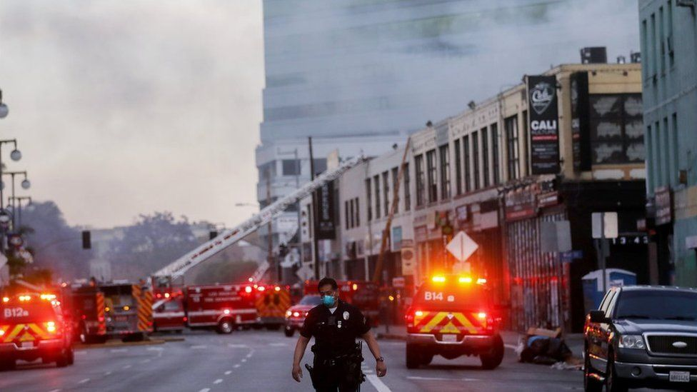 An LAPD officer keeps watch on a multiple structure fire as LAFD firefighters work following an explosion on May 16, 2020 in Los Angeles, California