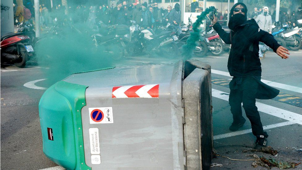 A protester throws a smoke bomb towards police during scuffles at a Catalan pro-independence demonstration in Barcelona on December 21, 2018
