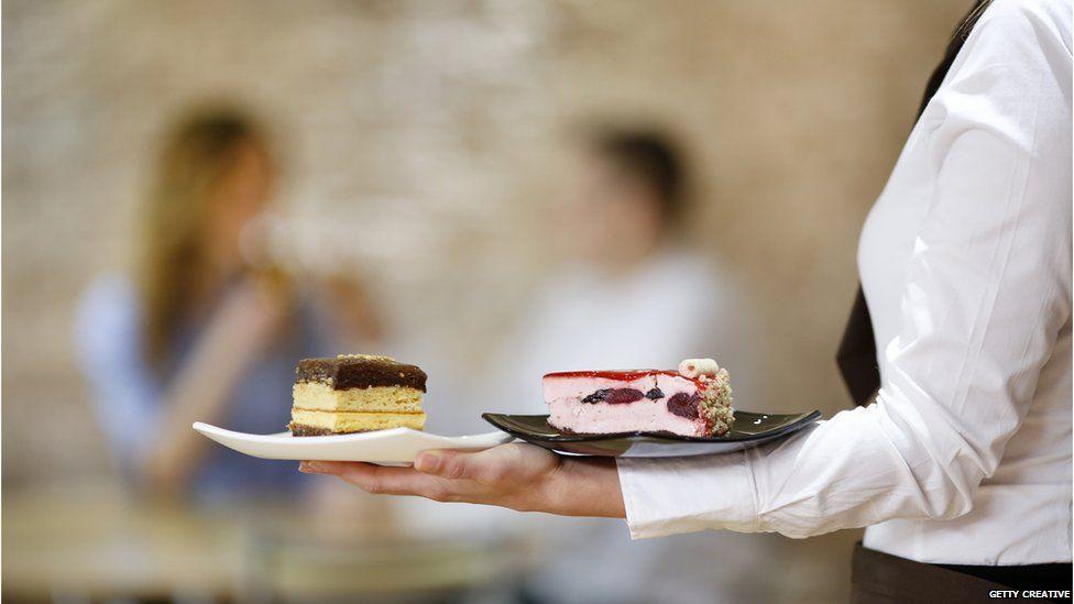 A waitress serves dessert