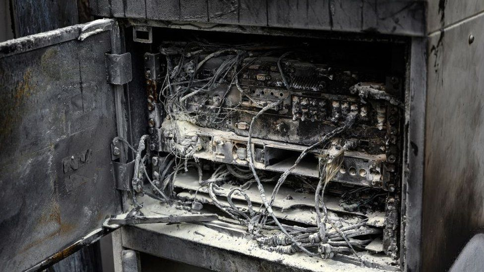 Damaged cabling and telecommunications equipment is pictured following a fire at a phone mast, attatched to the chimney at the converted Fearnleys Mill residential apartment block complex in Huddersfield, northern England, on April 17, 2020. -