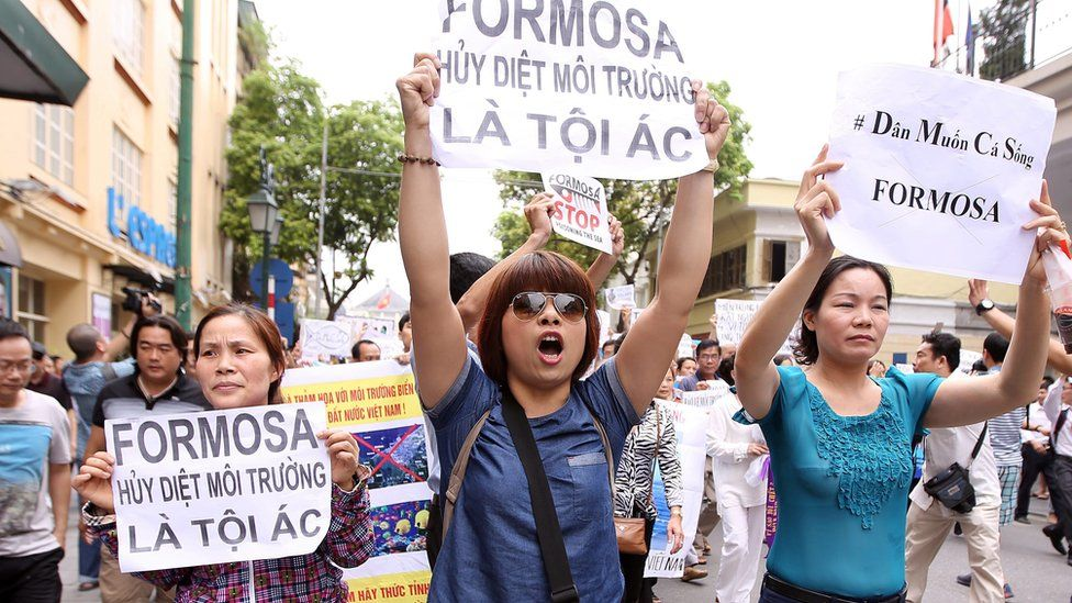 """Vietnamese protesters hold banners reading """"Formosa destroys the environment, which is a crime"""" during a rally in Hanoi on 1 May, 2016"""