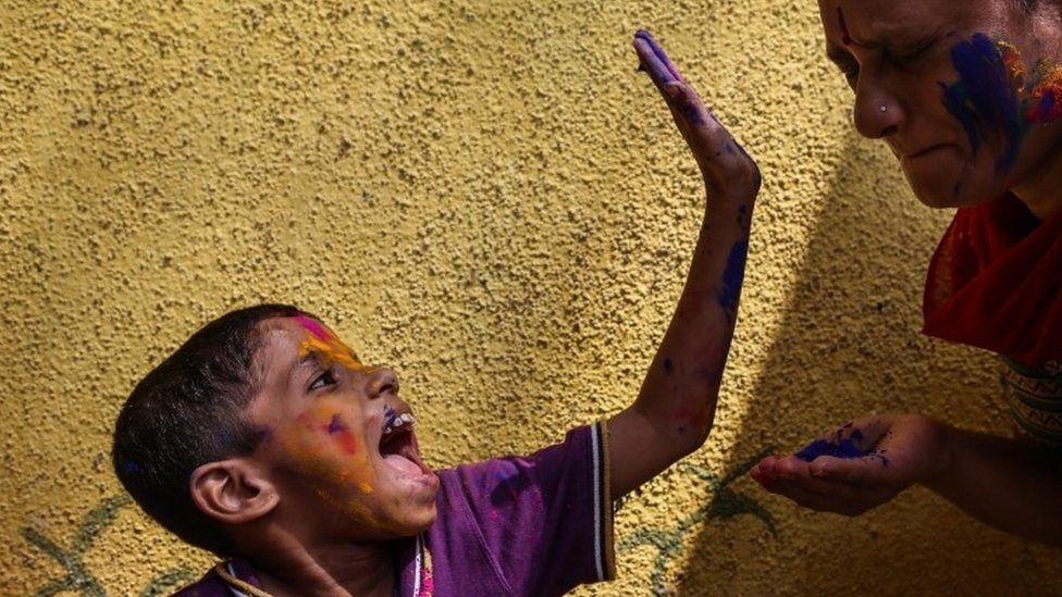 "Physically and mentally disabled Indian children have their faces smeared with powdered colours during the Holi festival celebrations at the special school ""Society for the Education of the Crippled"" in Mumbai, India, 23 March 2016."
