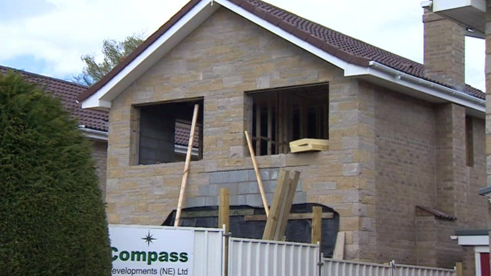 House with two empty windows in the process of being rebuilt