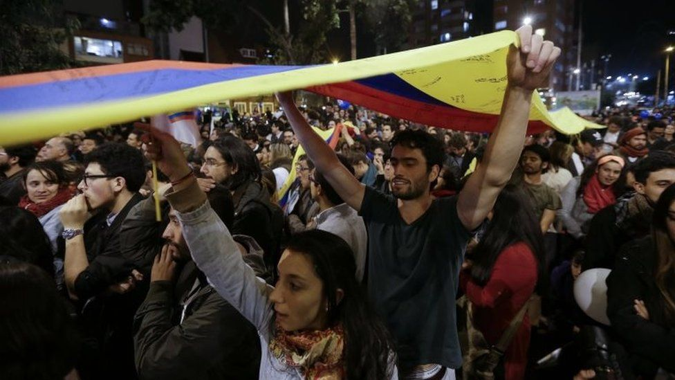 People celebrate the announcement from Havana, Cuba, that delegates of Colombia's government and leaders of the Revolutionary Armed Forces of Colombia reached a peace accord to end their half-century civil war, in Bogota, Colombia, Wednesday, Aug. 24, 2016.