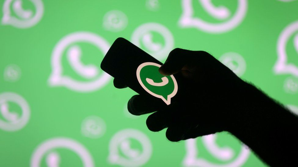 A silhouetted hand useds a smartphone bearing the WhatsApp logo