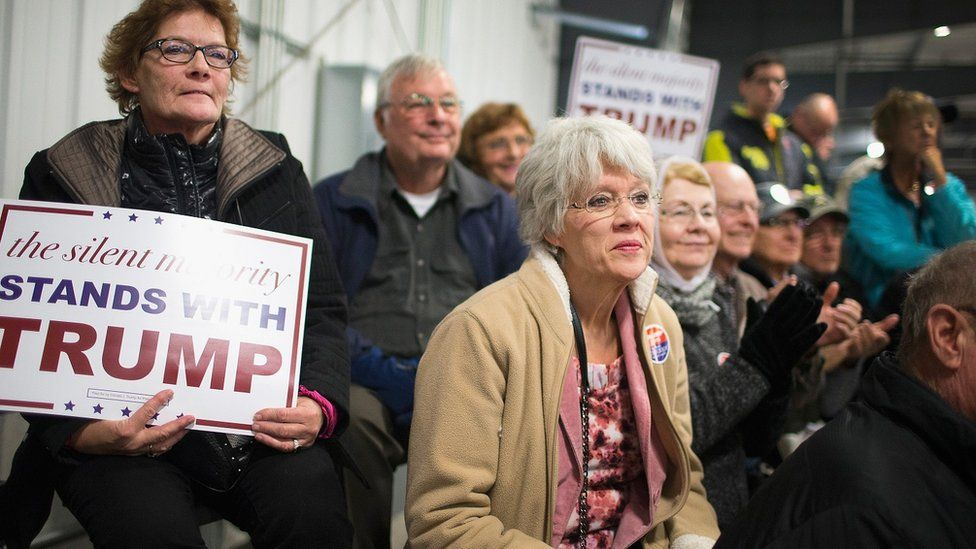 A group of sign-holding supporters listen to Donald Trump speak in Iowa.