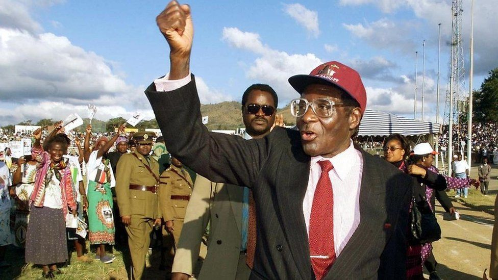 Robert Mugabe greets Zanu PF followers on his arrival for a rally in the city of Mutare some 290 km east of the capital Harare, 09 June 2000