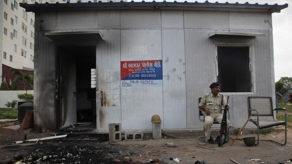 An Indian policeman sits outside a damaged police post that was set on fire during clashes in Ahmadabad, India, Wednesday, Aug. 26, 2015
