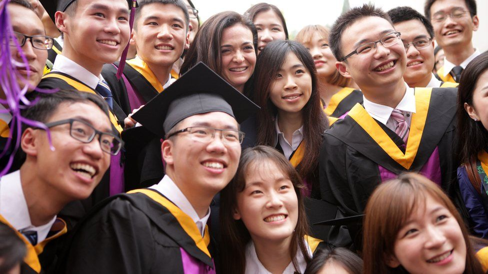 Sheryl Sandberg poses with students at a graduation ceremony in Beijing China in 2015