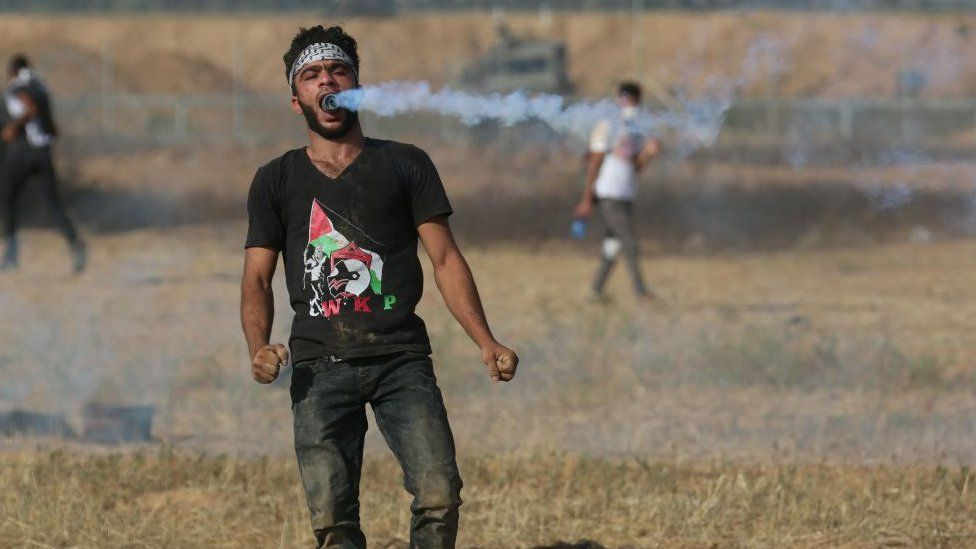 A protester in Gaza holds a can of gas in his mouth during clashes in June 2018