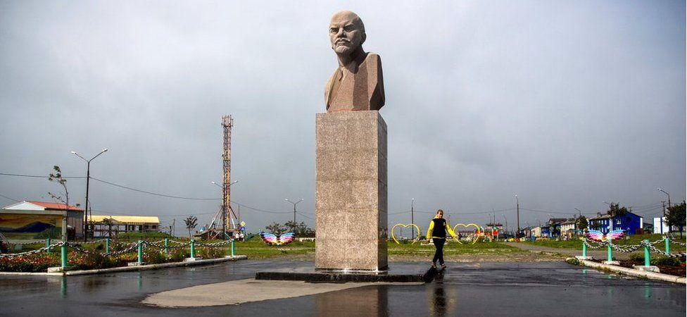 A woman walks past a Lenin statue in Yuzhno-Kurilsk, the main settlement on the southern Kuril island of Kunashir, 7 September 2015.
