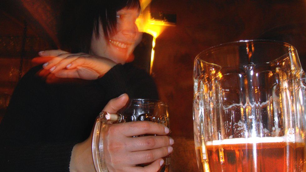 Woman drinking beer in a Moscow bar