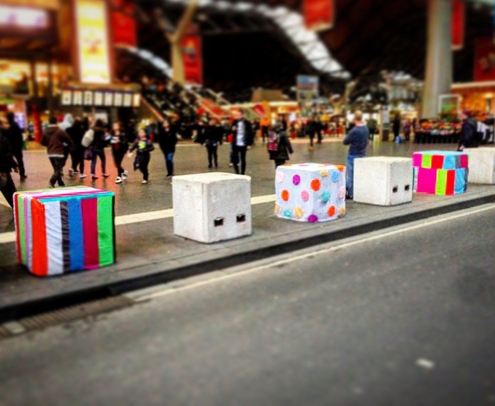 Concrete bollards covered in colourful fabric