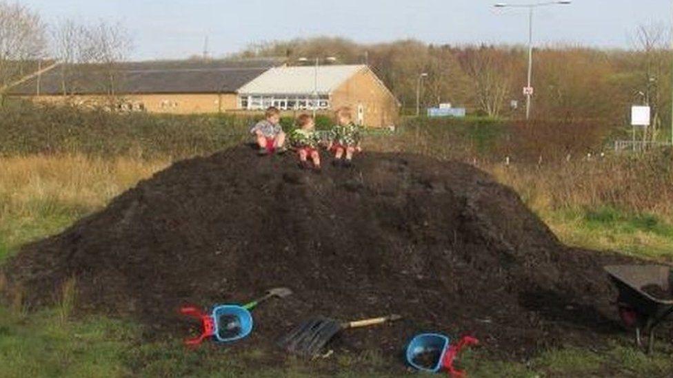 Kamran, Kaydan and Levi climb a mountain of compost at Badgers Brook
