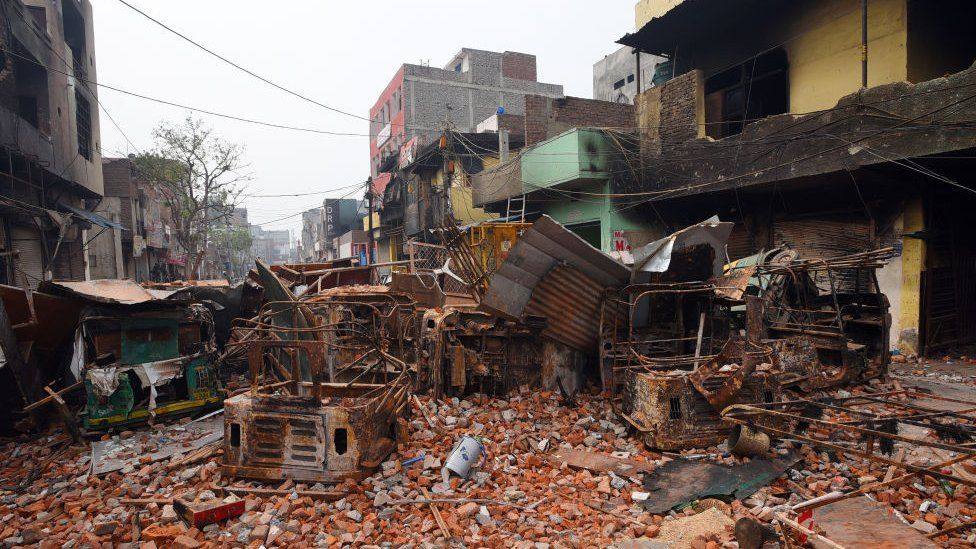 Police walk on debris at a riot affected area of Shivpuri following the Citizenship Amendment Act (CAA) clashes in Delhi
