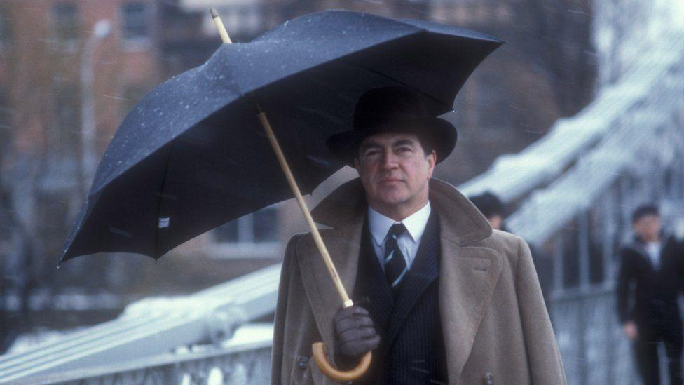 Alan Bates with an umbrella in the rain