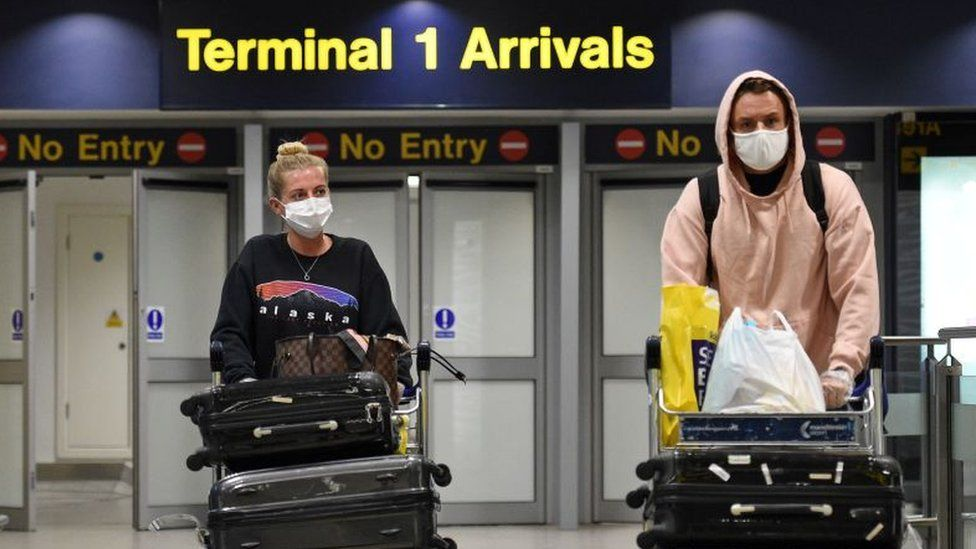 Passengers wearing PPE (personal protective equipment), including a face mask as a precautionary measure against COVID-19, arrive at Terminal 1 of Manchester Airport