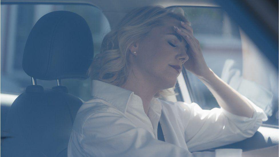An upset woman in a car
