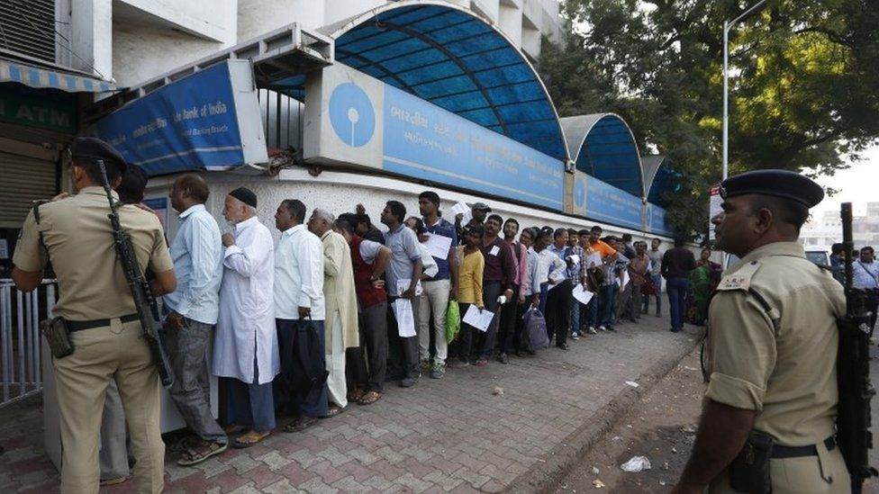 Indian policemen stand guard as people queue up outside a bank to exchange and deposit Indian currency of rupees 500 and 1000 denominations in Ahmadabad, India, Thursday, Nov. 10, 2016.