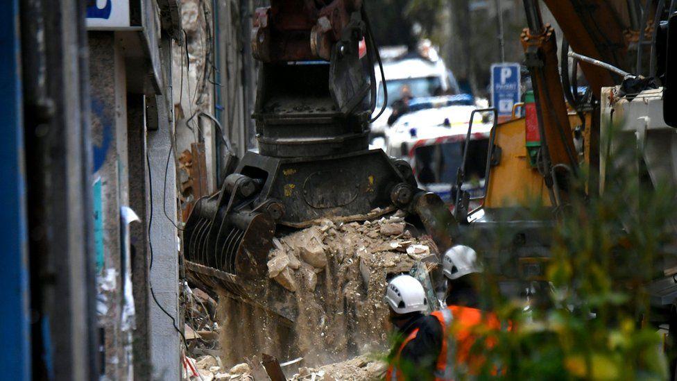 A large digger picks up large amounts of debris spilling dust