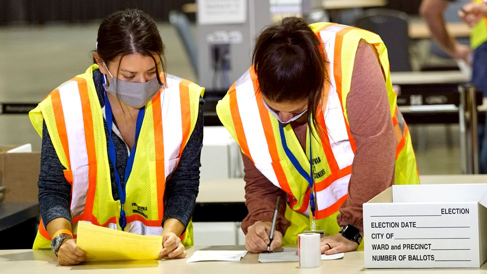 Two electoral workers count ballots on a table