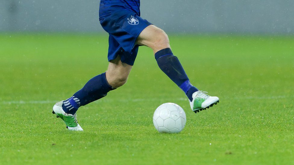 Footballer playing with football