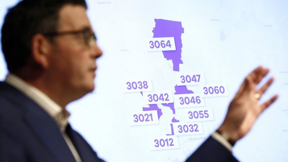 Victorian premier Daniel Andrews stands in front of a powerpoint slide listing the postcode hotspots on a map