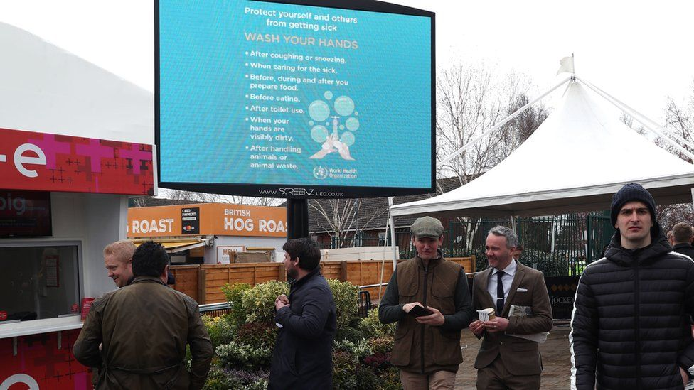 Racegoers pass a sign referencing how to protect yourself and others from getting sick following the Coronavirus outbreak ahead on day one of the Cheltenham Festival at Cheltenham Racecourse