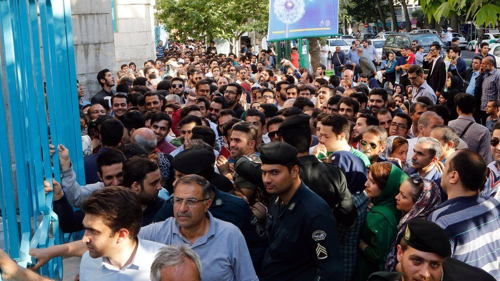 Iranians wait in a line to cast their ballots in the Iranian presidential elections outside a polling station in Tehran, Iran, 19 May 2017.