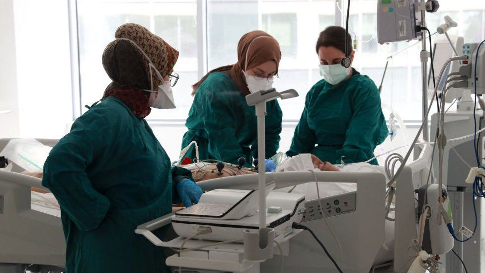 Three masked medical workers tend to a patient in an intensive care unit in Ankara