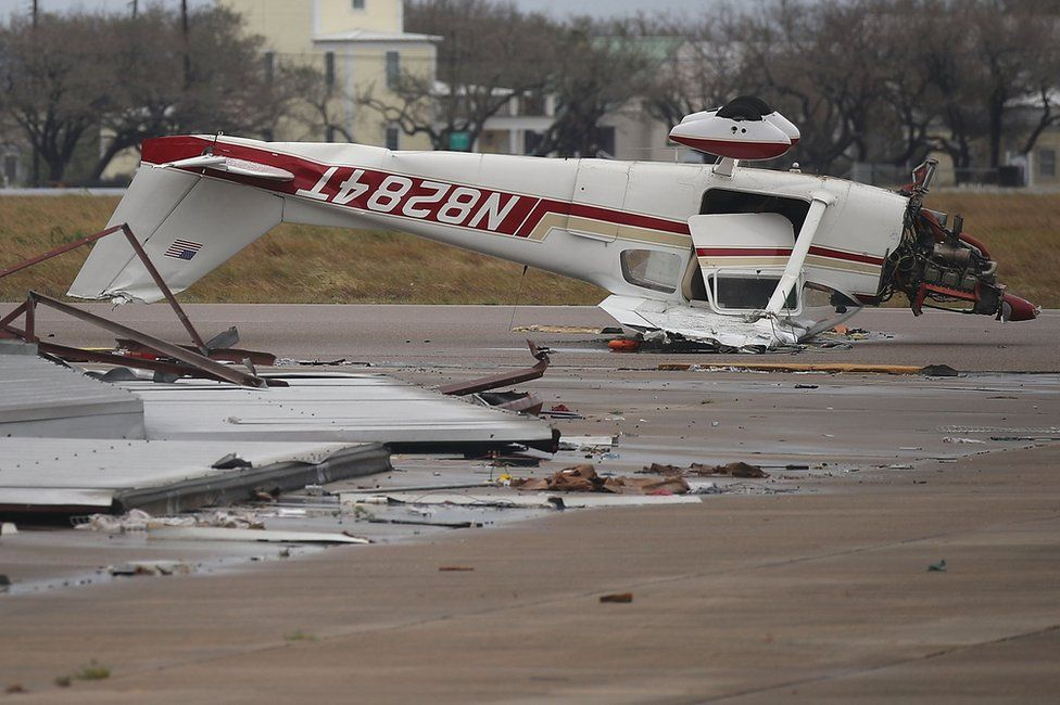 An airplane is seen flipped on its roof at Aransas County Airport after Hurricane Harvey passed through on 26 August
