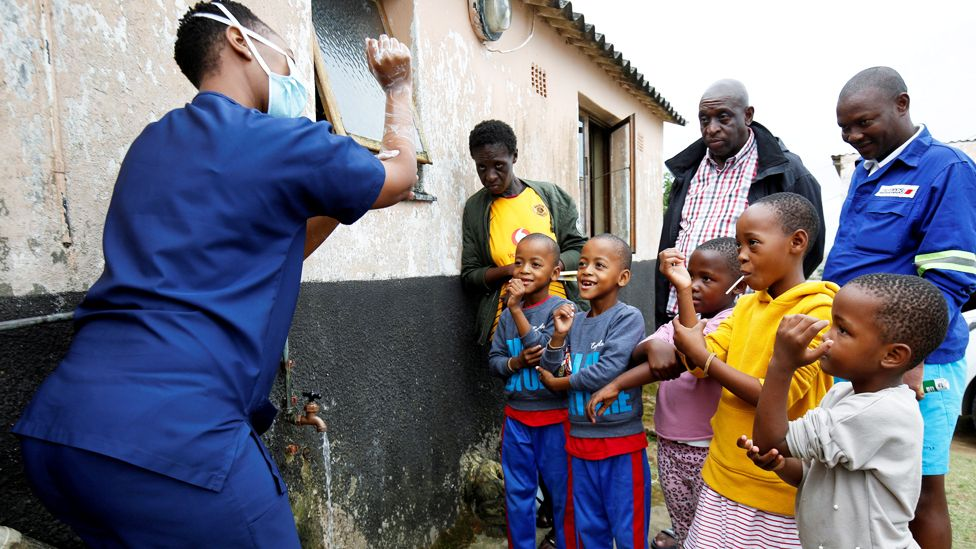 A health worker teaches children how to wash their hands in Umlazi township, South Africa - Saturday 4 April 2020