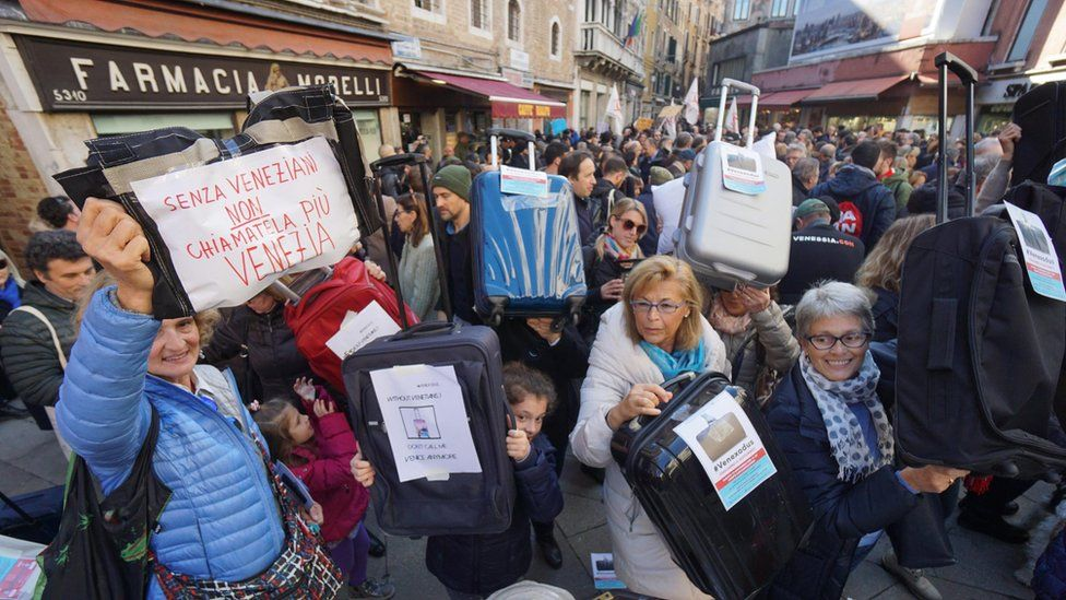 """Residents of Venice hold luggages during the """"Venexodus"""" demonstrations in Venice, Italy, 12 November 2016"""
