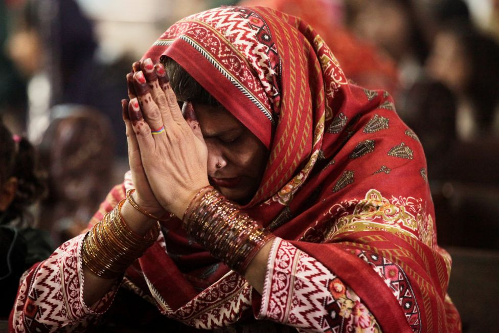 A woman prays during a Christmas service at the Sacred Heart Cathedral in Lahor