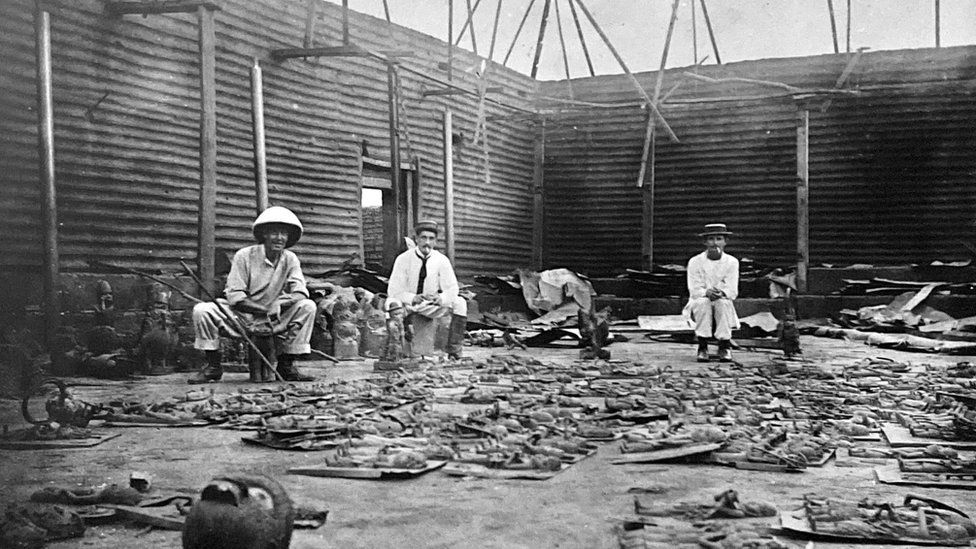 Interior of the Royal Palace during looting in February 1897, showing Captain Charles Herbert Philip Carter, EP Hill, and an unnamed man, with bronzes laid out on the floor.