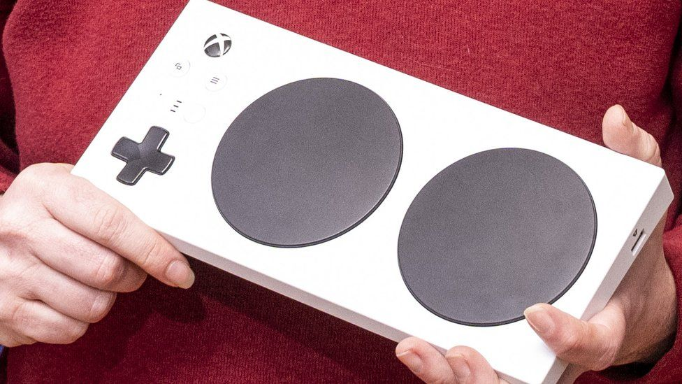 This close-up shot of a Xbox adaptive controller being held shows the white rectangle, dominated by two large circular buttons - with extra ports for add-ons on the side