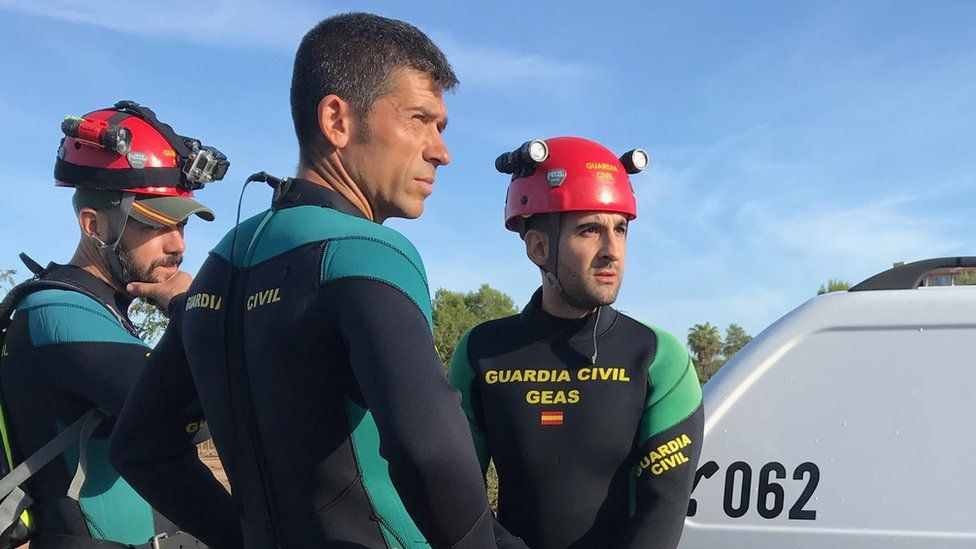 Three men in wetsuits and hard hats, emblazoned with the logo of the Spanish civil guard, stand by their vehicle