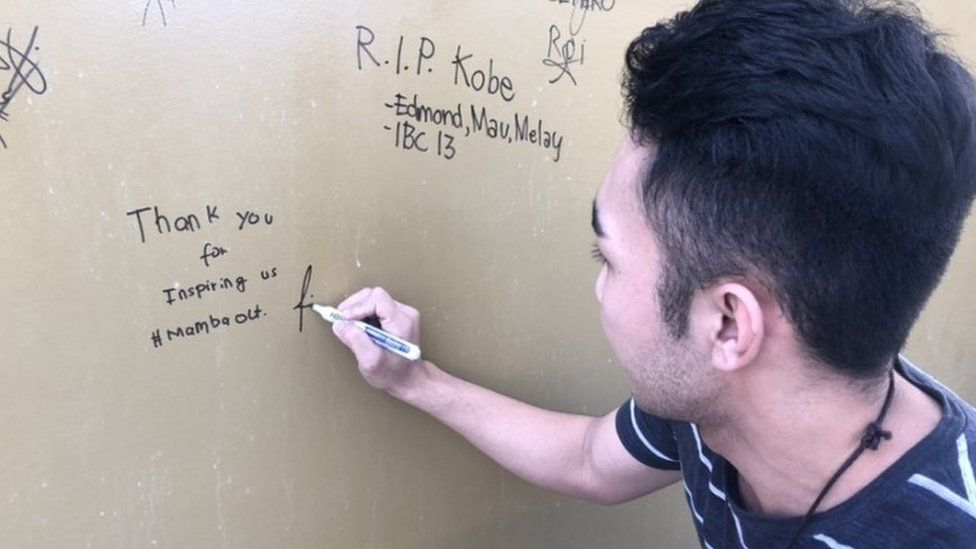 A fan writes a message to Kobe Bryant on the wall of the World of Kobe in Manila