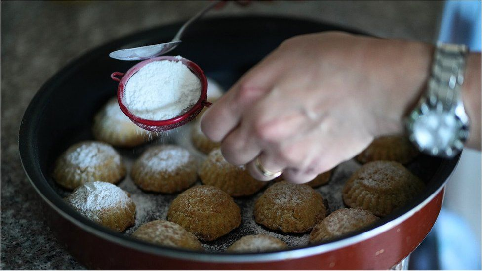 Date maamoul being topped with icing sugar