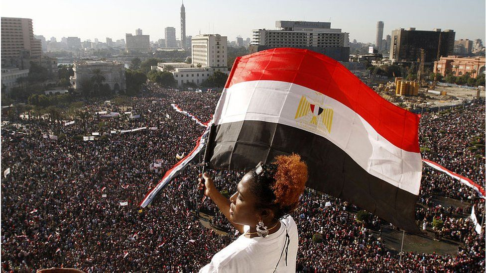 A woman waves an Egyptian flag overlooking crowds in Tahrir Square, Cairo (Feb 2011)