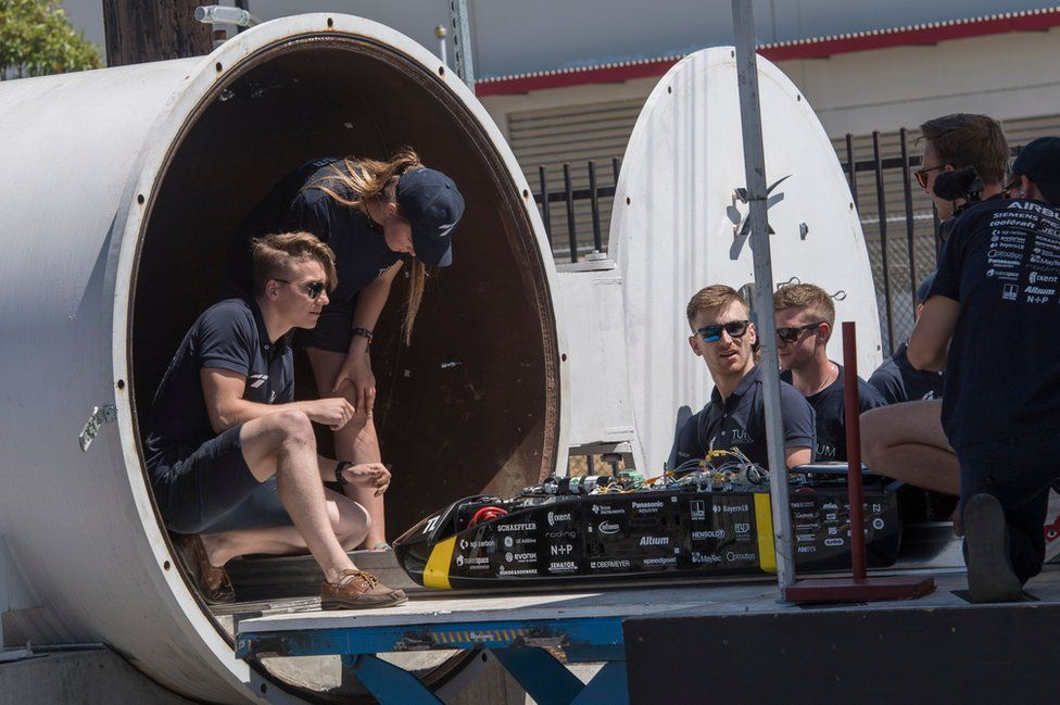 A handful of students sit in the mouth of a SpaceX tunnel with their pod