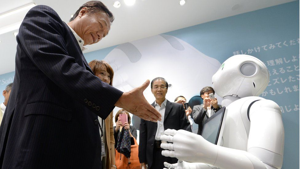 Terry Gou (L), chairman and CEO of Taiwan's Foxconn Technology group, tries to shake hands with humanoid robot 'Pepper' (R), which is jointly developed by Japan's mobile carrier SoftBank and French humanoid robot maker Alderbaran and manufactured by Foxconn, at a showroom of SoftBank in Tokyo, on 6 June 2014.