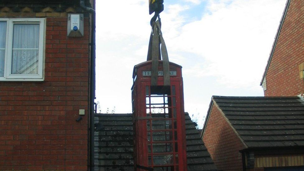 Steve Spill's phone box lifted over the house by a crane