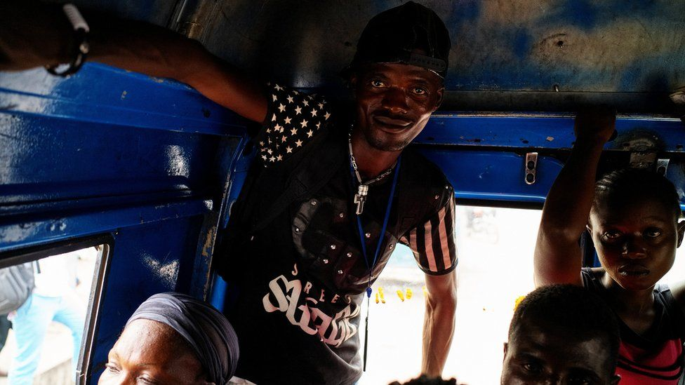 A passenger stands as another sits, holding on to the inside roofline of the taxi-van as they ride to their destinations of Limete Municipality in Kinshasa, Democratic Republic of Congo, September 12, 2017
