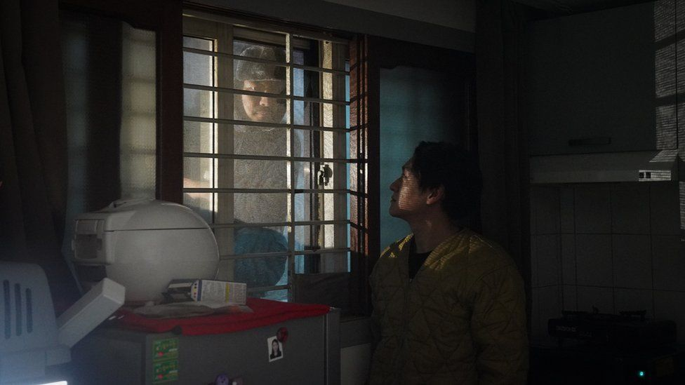 Person looking through the window of Oh kee-cheol's apartment
