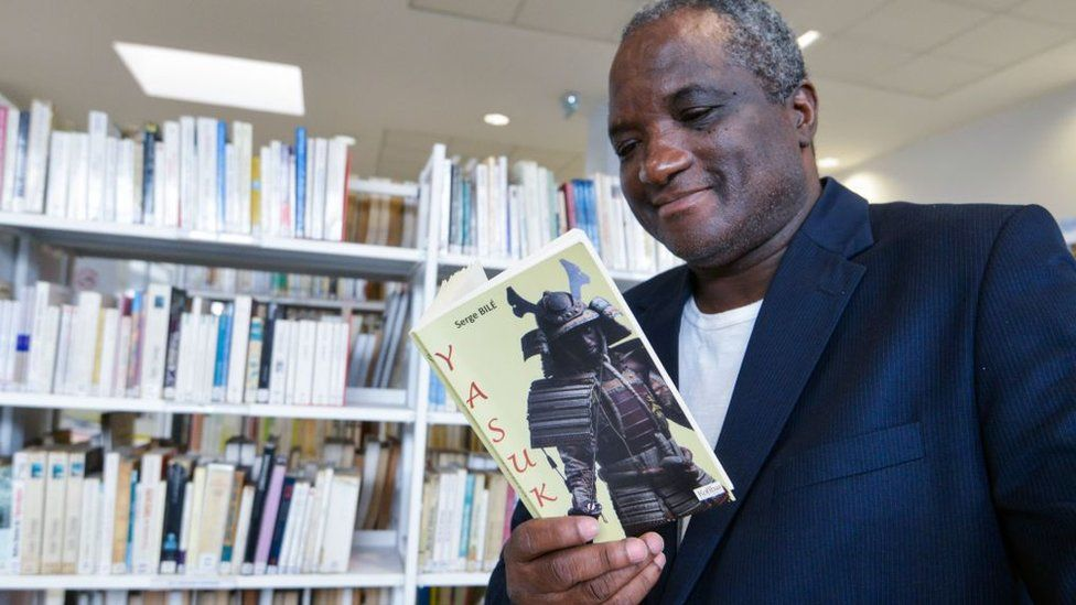 """French-Ivorian writer Serge Bile reads a copy of his last book """"Yasuke"""" at the library of the French Cultural Centre (CCF) in Abidjan on 28 March 2018."""